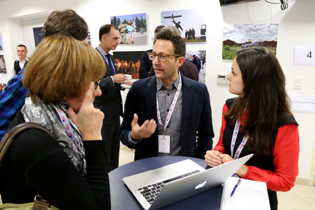 Participants speak with a trainer at TechForum Ukraine.