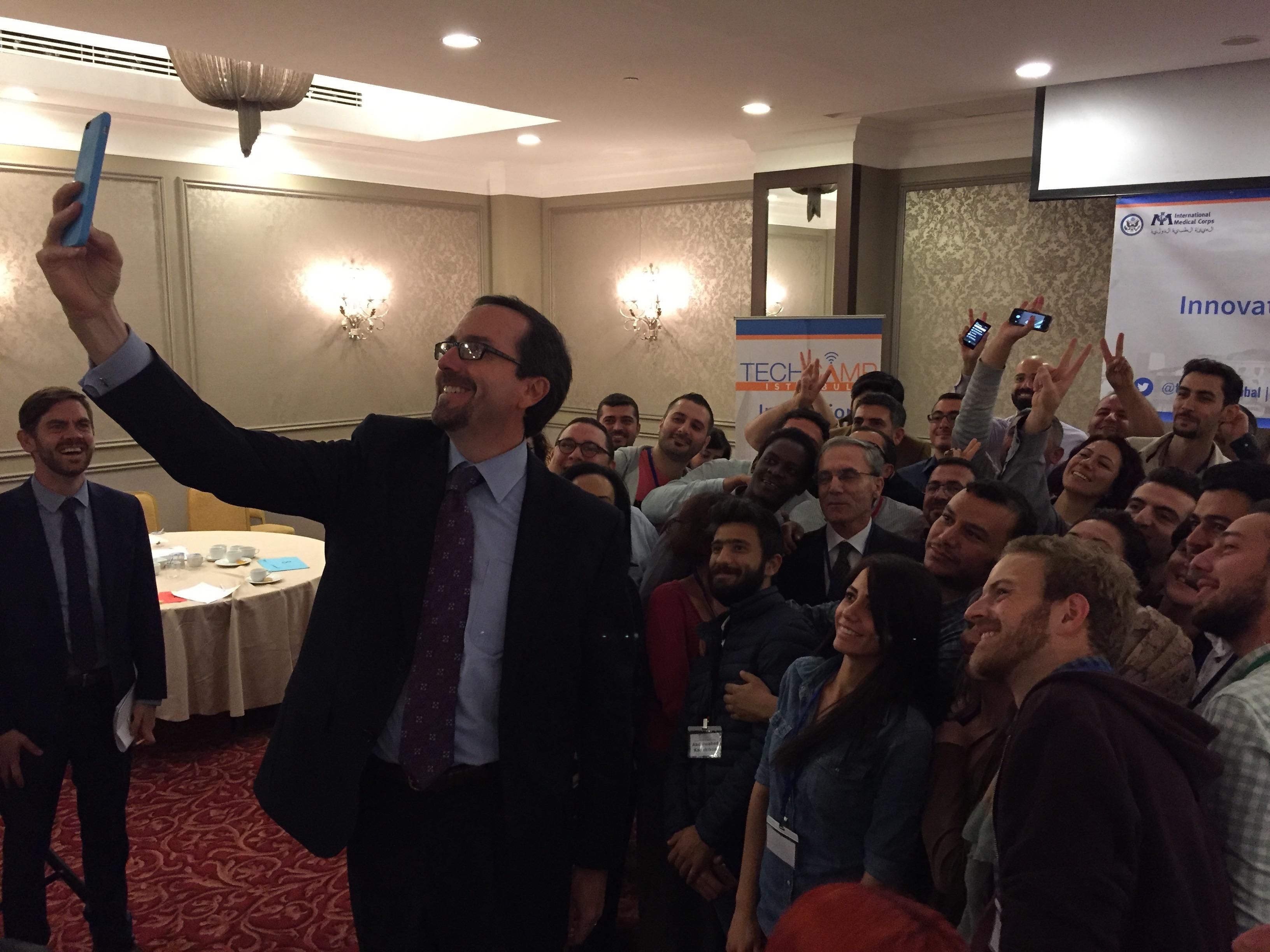 Ambassador John Bass takes a selfie with TechCamp Istanbul participants.