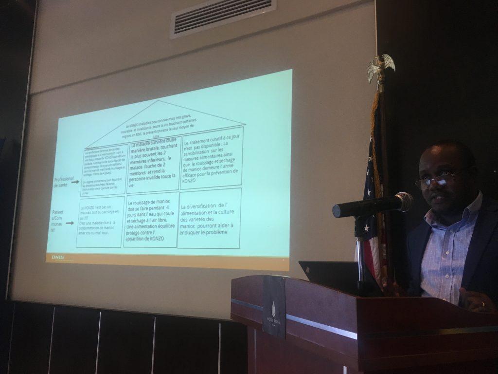 A TechCamp participant at a podium gives a presentation on Konzo.